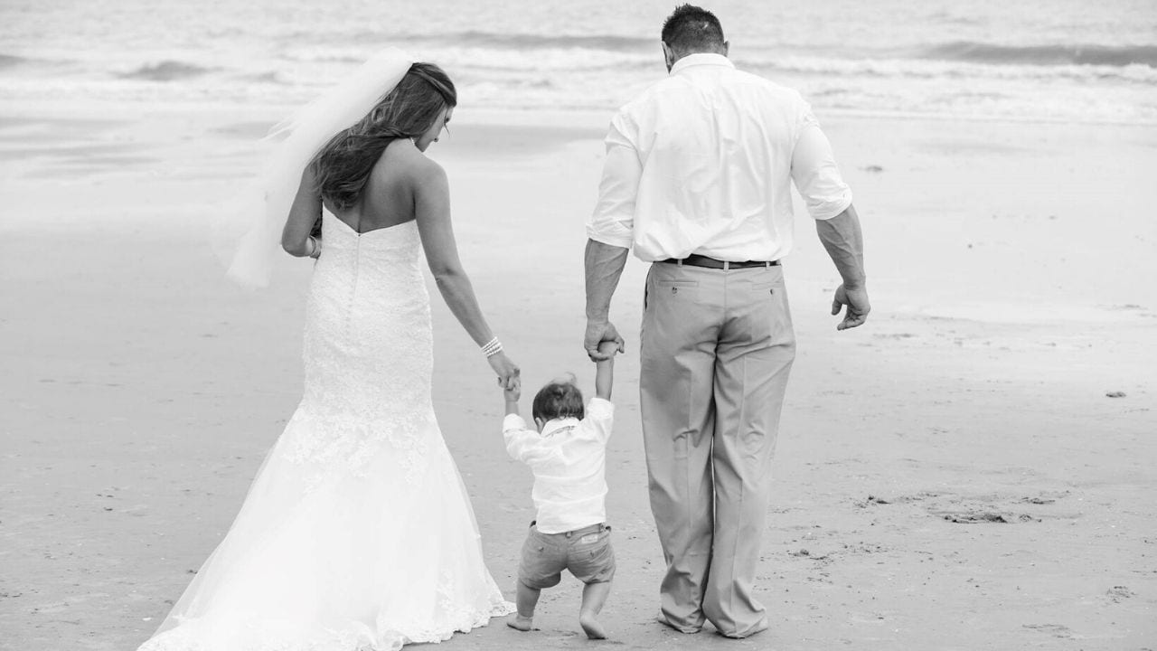 Bride, groom, and son on the beach