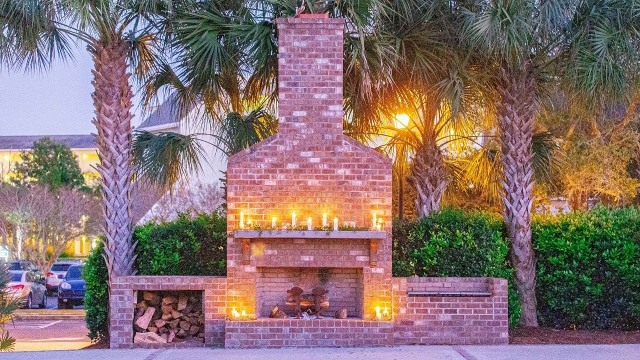 Fireplace in courtyard at night with candles