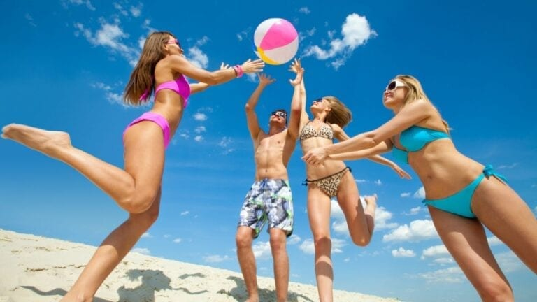 Teens playing beach volleyball
