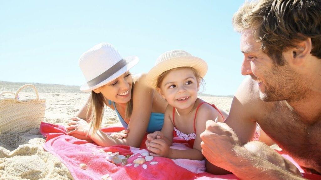 Family on a beach towel on sand