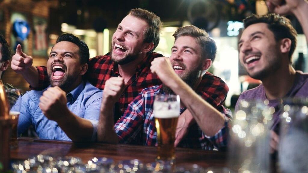 Four guys cheering at a bar