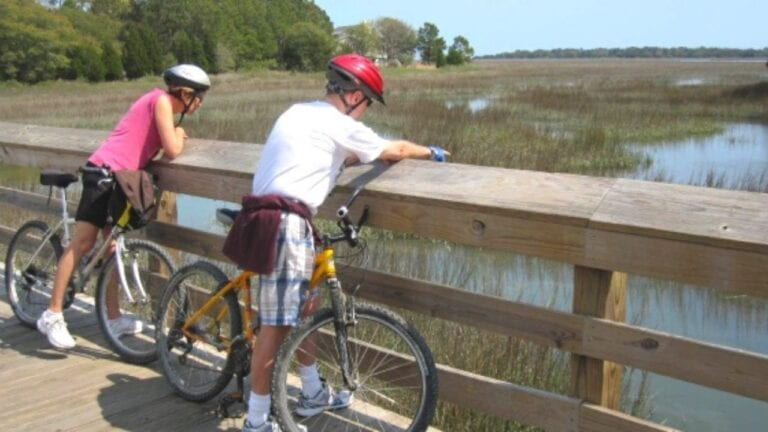 Man and woman riding bikes on bridge over marsh
